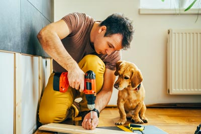 Man drilling while his dog watches