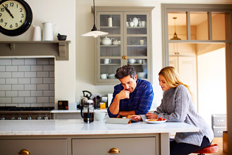 A couple sitting at their kitchen counter studying their tablet