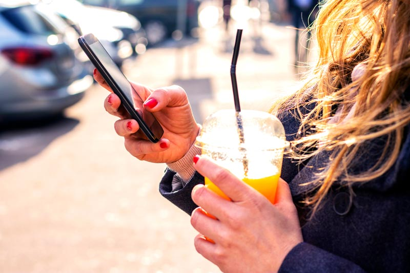 Girl outside with tea and a mobile phone on a sunny day