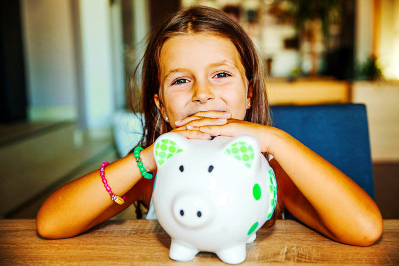 A little girl with her piggy bank